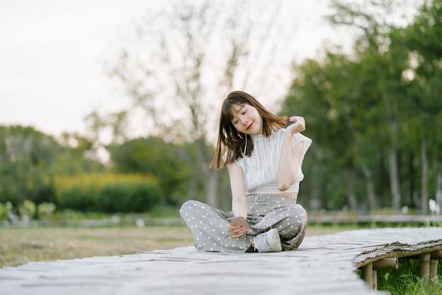 Giovane donna sorridente in abiti bianchi con auricolari seduto sul passaggio pedonale in legno nel parco e godendo il suo momento mentre si utilizza il telefono cellulare ascoltando musica con gli occhi guardando lo schermo Foto Premium