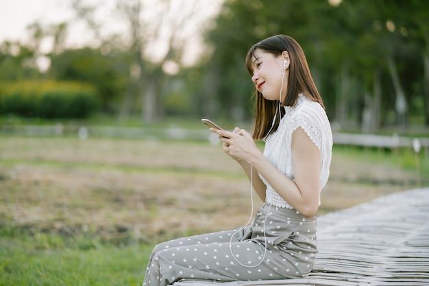 Giovane donna sorridente in abiti bianchi con auricolari seduto sul passaggio pedonale in legno nel parco mentre si utilizza il telefono cellulare ascoltando musica con gli occhi guardando lontano dalla fotocamera in vena rilassante e felice Foto Premium