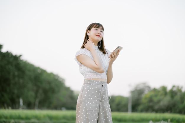 Giovane donna sorridente in abiti bianchi con auricolari in piedi nel parco mentre si utilizza il telefono cellulare ascoltando musica con gli occhi guardando qualcosa di interessante nell'umore rilassante e felice Foto Premium