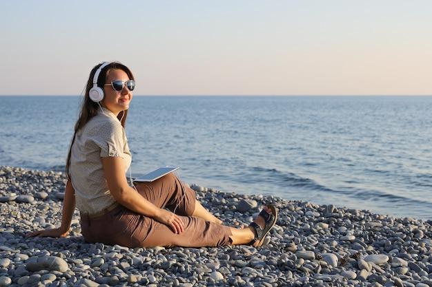 Giovane donna sorridente in cuffie bianche e occhiali da sole ascoltando musica sulla spiaggia di ciottoli Foto Premium
