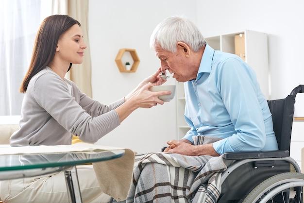 Giovane assistente sociale che tiene ciotola con minestra e cucchiaio per bocca di anziano disabile uomo seduto in sedia a rotelle mentre lo aiuta a mangiare Foto Premium
