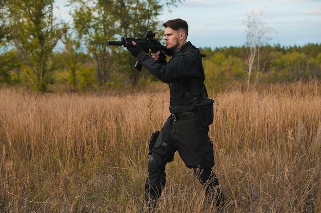 Giovane soldato in uniforme nera che mira un fucile d'assalto Foto Premium