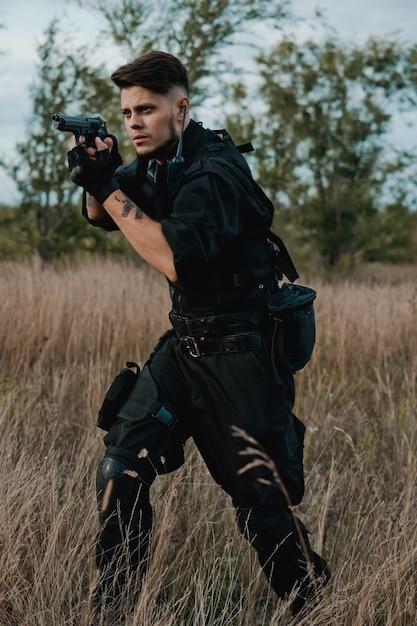 Giovane soldato in uniforme nera che mira una pistola Foto Premium