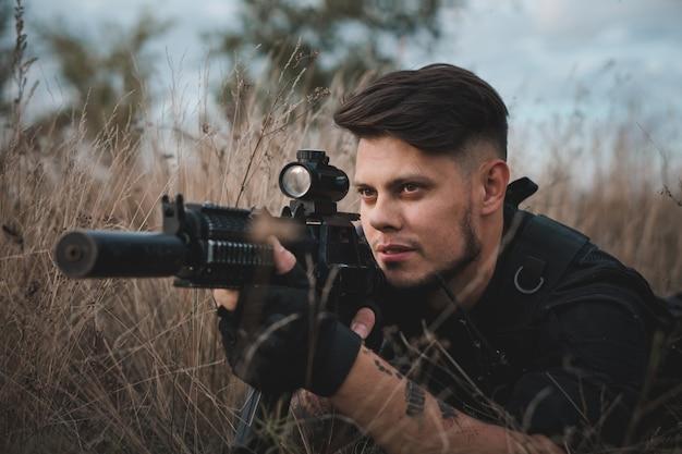 Giovane soldato in uniforme nera sdraiato e puntando un fucile d'assalto Foto Premium