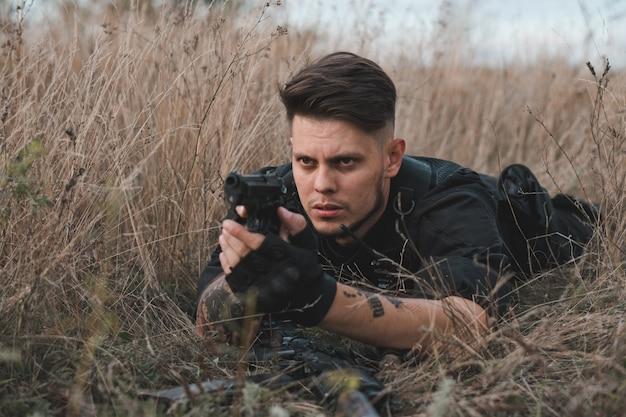Giovane soldato in uniforme nera sdraiato e puntando una pistola Foto Premium
