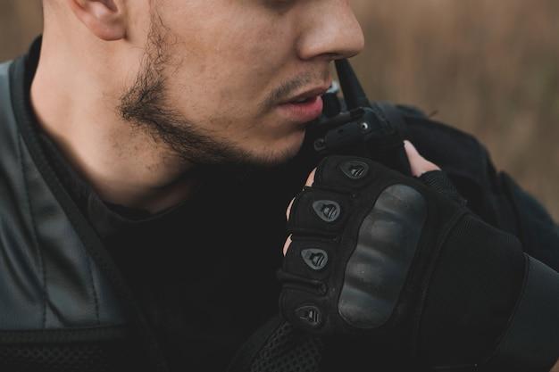 Giovane soldato in uniforme nera che fa rapporto alla radio Foto Premium