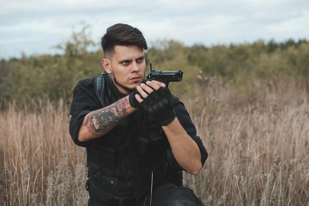 Giovane soldato in uniforme nera che si siede e che mira una pistola Foto Premium