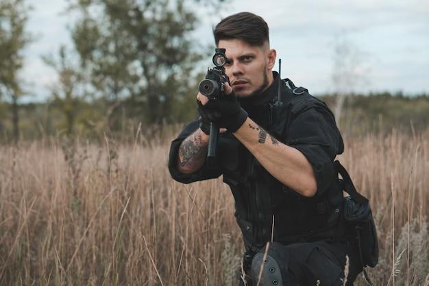 Giovane soldato in uniforme nera che si siede e mira con un fucile d'assalto Foto Premium