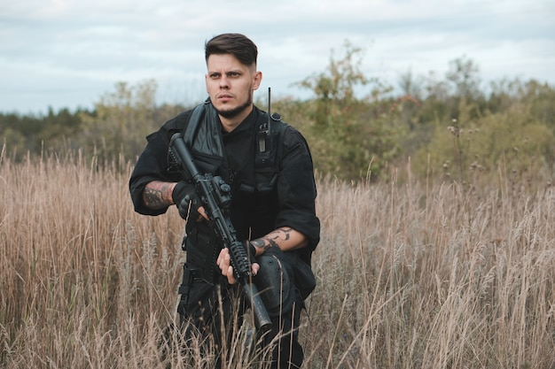 Giovane soldato in uniforme nera che si siede con un fucile d'assalto Foto Premium