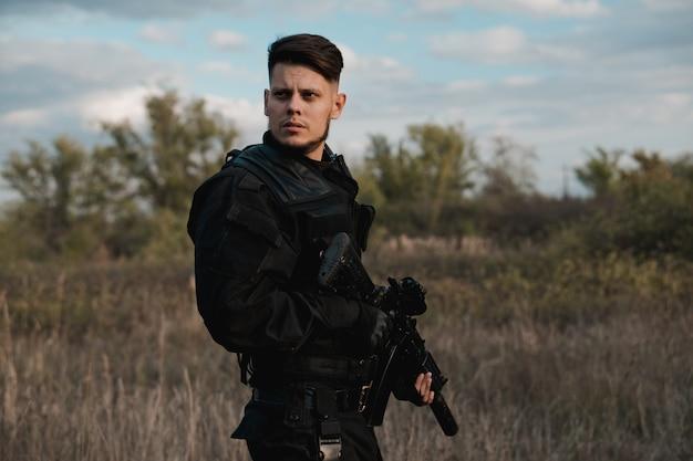 Giovane soldato in uniforme nera con un fucile d'assalto Foto Premium
