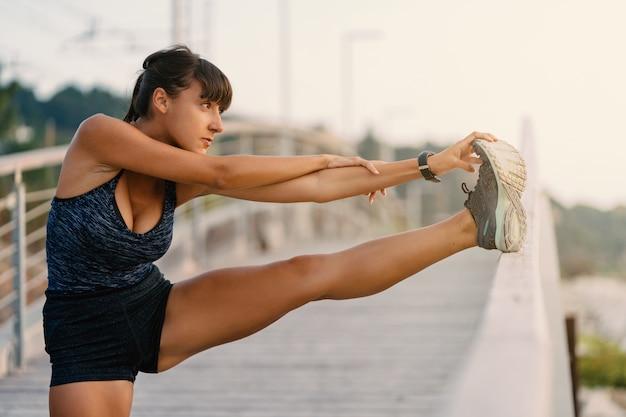 Giovane donna di sport che fa allungando all'aperto su un ponte di mattina Foto Premium