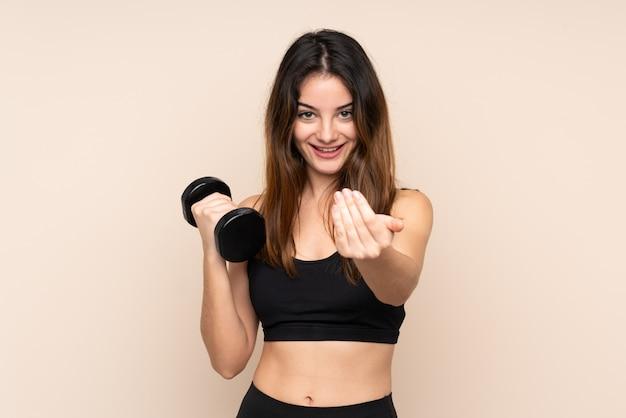 Giovane donna di sport che fa sollevamento pesi isolato sull'invito beige a venire Foto Premium
