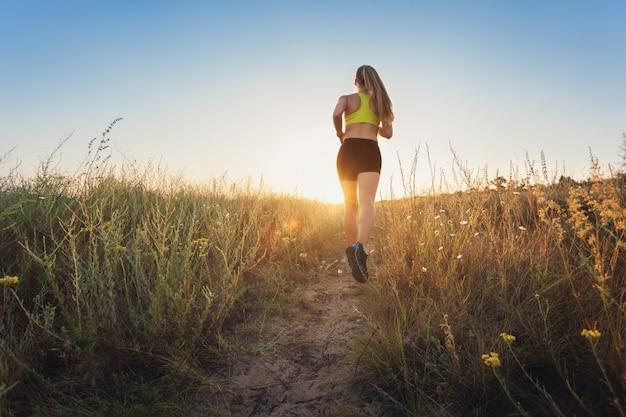Giovane donna sportiva che funziona su una strada rurale al tramonto Foto Premium