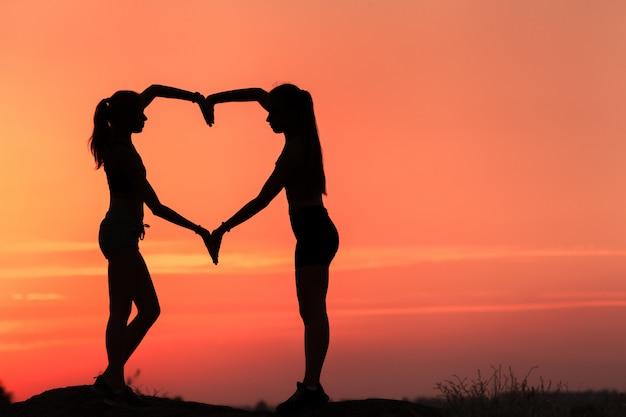 Le giovani donne sportive che si tengono per mano nel cuore modellano al tramonto Foto Premium