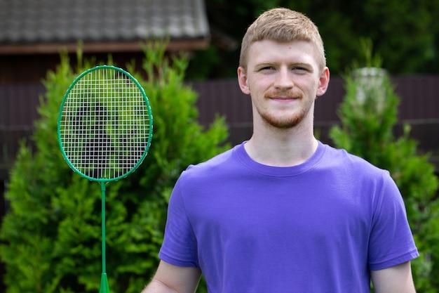 Uomo caucasico di giovane sport forte che posa con la racchetta di badminton sulla natura verde. concetto di gioco amatoriale di badminton, attività estive all'aperto. Foto Premium