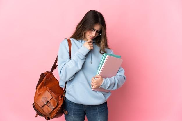 Giovane donna dell'allievo isolata sul colore rosa che ha dubbi Foto Premium