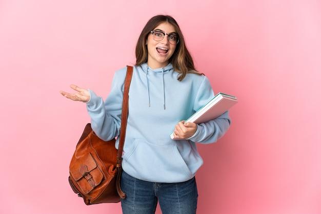 Donna giovane studente in rosa con espressione facciale scioccata Foto Premium