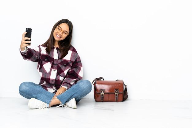 Giovane donna dello studente che si siede sul pavimento che fa un selfie Foto Premium