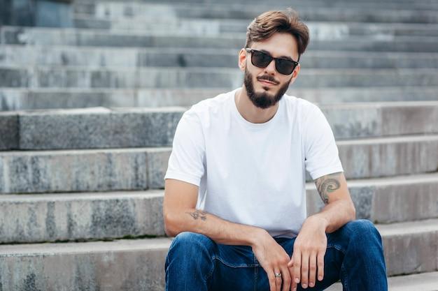 Un giovane uomo alla moda con la barba in maglietta bianca e occhiali Foto Premium