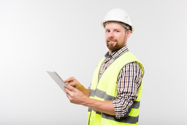 Giovane costruttore barbuto di successo in elmetto protettivo bianco, camicia a scacchi e giubbotto giallo utilizzando tablet davanti alla telecamera Foto Premium