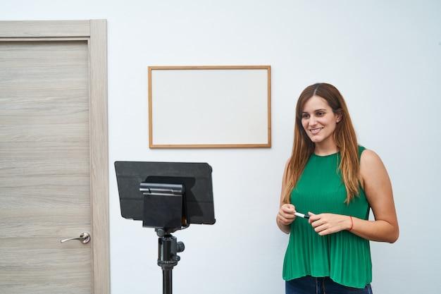 Giovane insegnante che dà lezioni online a casa tramite videochiamata. concetto di nuove tecnologie, studio e lezioni online. Foto Premium