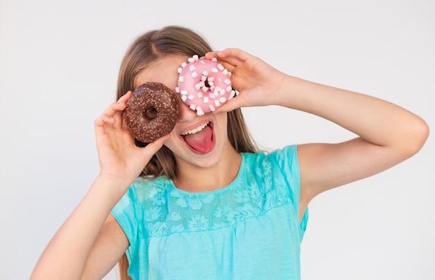 La giovane ragazza teenager con un'espressione giocosa mette le ciambelle ai suoi occhi Foto Premium