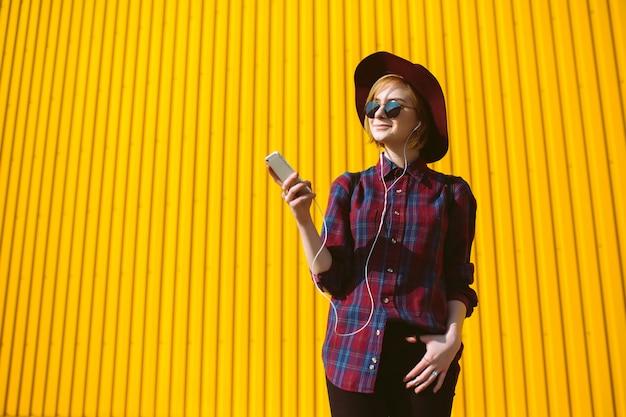 Giovane ragazza dell'adolescente con la bevanda e telefono in sue mani che posano sopra il fondo giallo variopinto vuoto. ragazza hipster Foto Premium