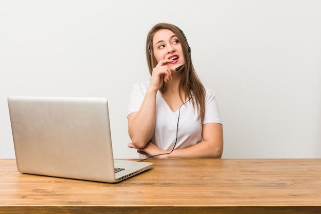 La giovane donna di telemarketer si è rilassata pensando a qualcosa guardando uno spazio di copia. Foto Premium