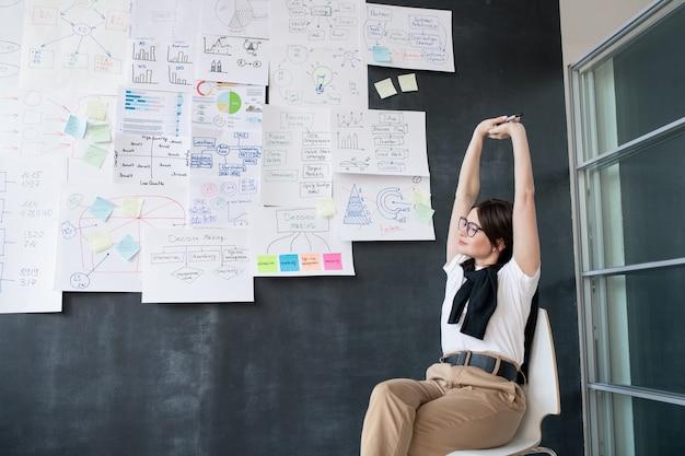 Giovane imprenditrice stanca che allunga le braccia mentre è seduto sulla sedia dalla lavagna e godendo di una breve pausa Foto Premium