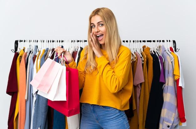 Giovane donna bionda uruguaiana in un negozio di abbigliamento e tenendo le borse della spesa sussurrando qualcosa Foto Premium