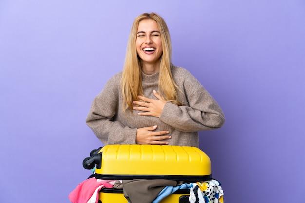 Giovane donna bionda uruguaiana con una valigia piena di vestiti sopra la parete viola isolata che sorride molto Foto Premium