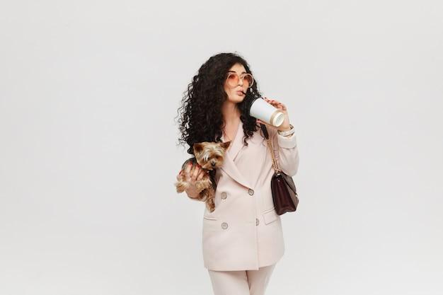 Una giovane donna in abito beige con in mano yorkie terrier e bevendo un caffè Foto Premium