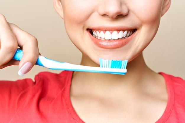 Giovane donna che pulisce i suoi denti Foto Premium