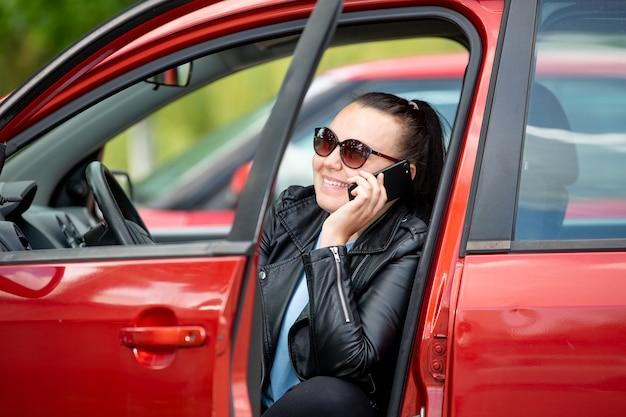 Giovane donna che chiama da cellulare, smartphone nel parcheggio auto, concetto di trasporto Foto Premium