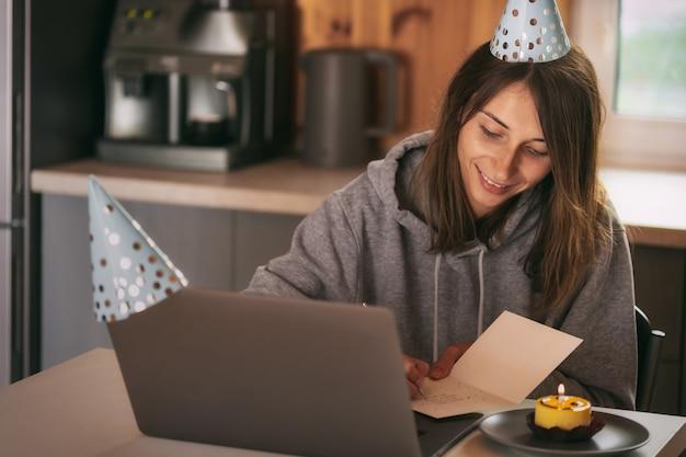 Giovane donna che celebra il suo compleanno a casa con gli amici in videochiamata Foto Premium