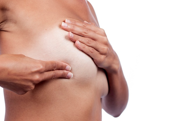 Giovane donna che controlla il seno (autoesame automatico) per anomalie, nodi o strani noduli per cancro al seno. Foto Premium