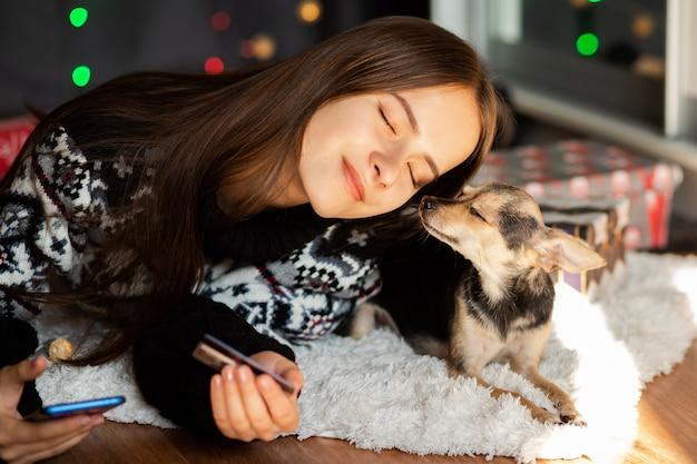 Una giovane donna in un maglione di natale con un piccolo cane abbraccia Foto Premium