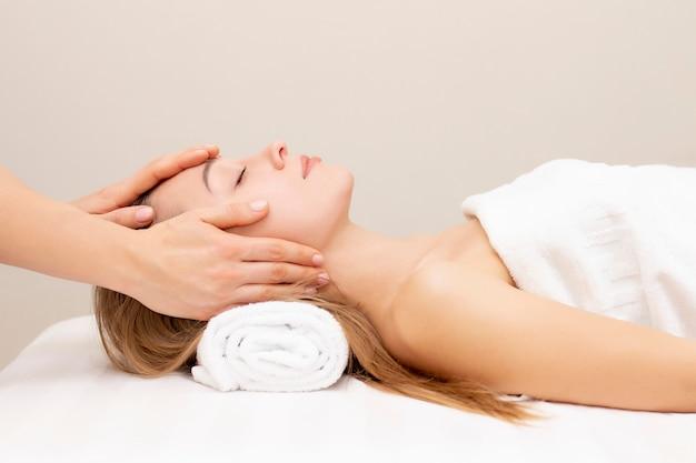 Giovane donna che gode del massaggio nel salone della stazione termale. massaggio viso. primo piano della giovane donna che ottiene trattamento di massaggio della stazione termale al salone della stazione termale di bellezza. cura della pelle e del corpo della stazione termale. trattamento di bellezza per il viso. cosmetologia. Foto Premium