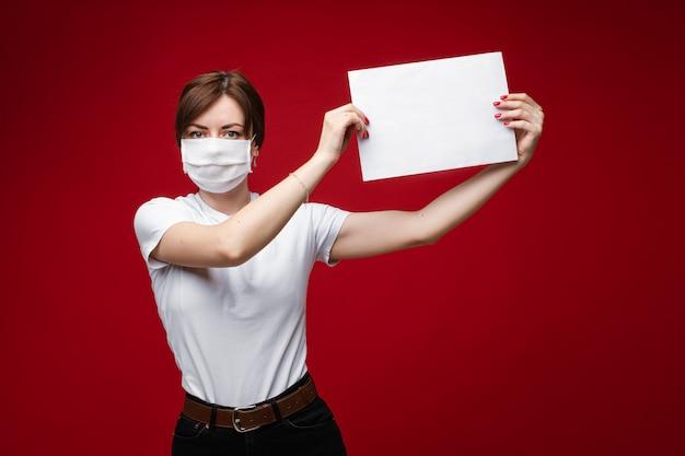 Giovane donna in maschera facciale per protezione dall'epidemia di virus che tiene la carta Foto Premium