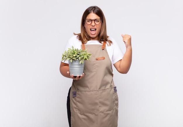 Giardiniere della giovane donna che grida in modo aggressivo con un'espressione arrabbiata o con i pugni chiusi per celebrare il successo Foto Premium