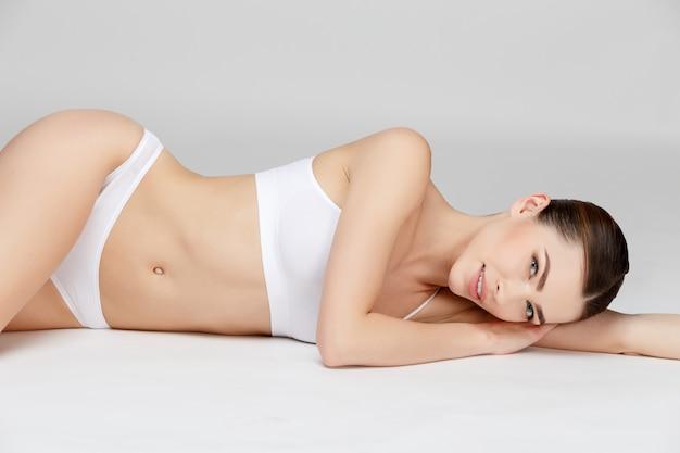 Giovane donna su grigio Foto Premium