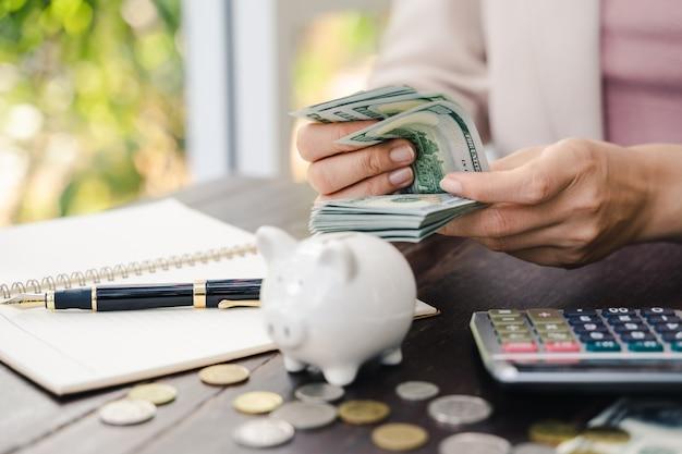 Mani della giovane donna che contano le banconote in dollari americani. risparmio di denaro e concetto finanziario Foto Premium