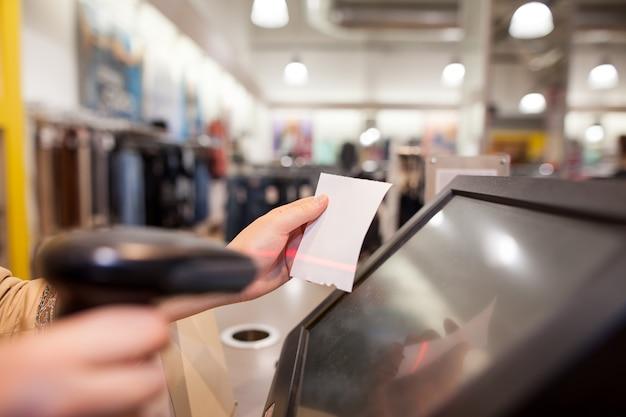 La giovane donna passa la scansione di un pagamento della bolletta per un cliente in un enorme centro commerciale Foto Premium