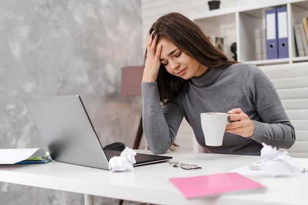 Giovane donna che ha un mal di testa mentre si lavora da casa Foto Premium