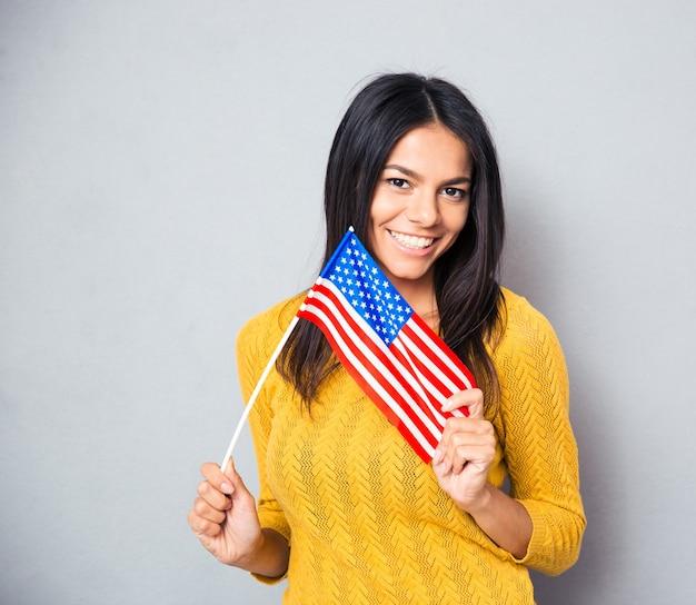 Giovane donna che tiene la bandiera americana Foto Premium