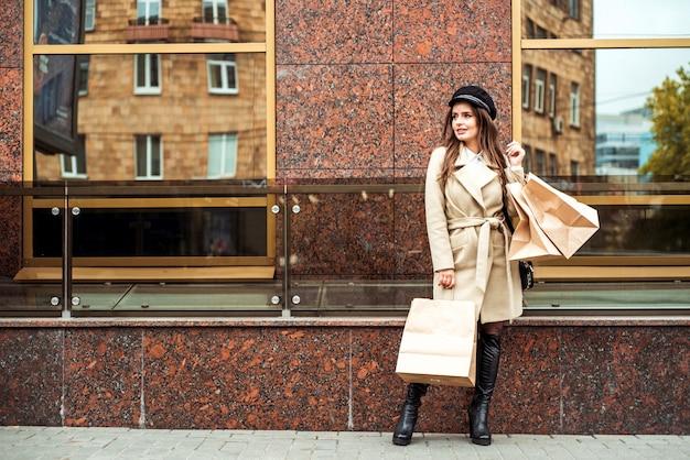 Sacchetti di shopping della holding della giovane donna nella via della città. la signora sorridente sta correndo con le grandi borse in metropoli consumismo, acquisto, vendite, concetto di stile di vita Foto Premium