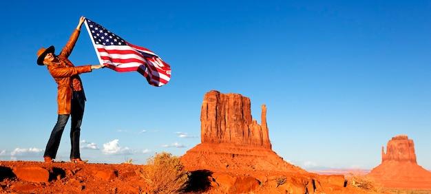 Giovane donna che tiene la bandiera usa alla monument valley Foto Premium