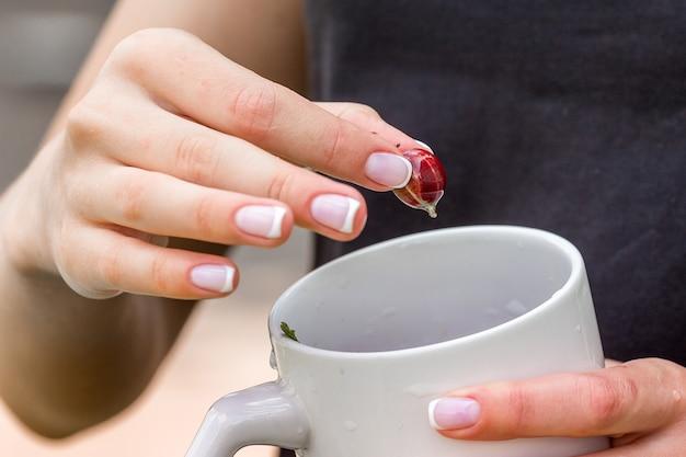 Una giovane donna tiene una tazza e una bacca di uva spina Foto Premium