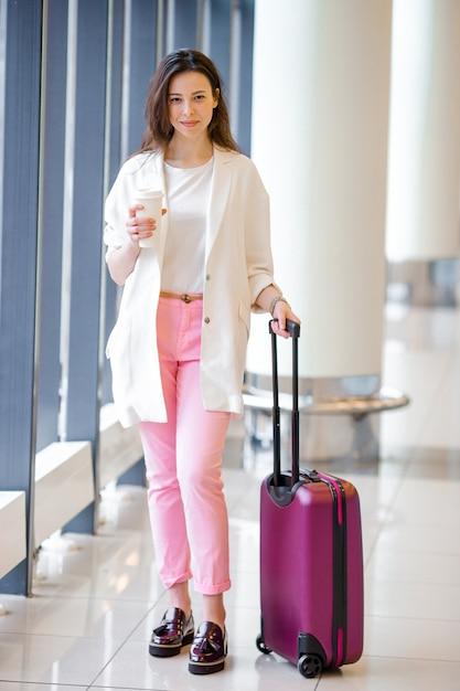 Giovane donna in aeroporto internazionale a piedi con i suoi bagagli e caffè per andare Foto Premium