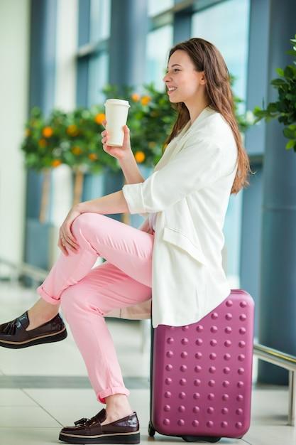 Giovane donna in aeroporto internazionale con i suoi bagagli e caffè per andare in attesa del suo volo Foto Premium